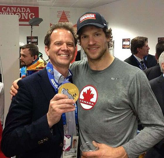 Coyotes Co-Owner George Gosbee and Mike Smith pose with Smith's gold medal at the 2014 Winter Olympics on Feb. 23.