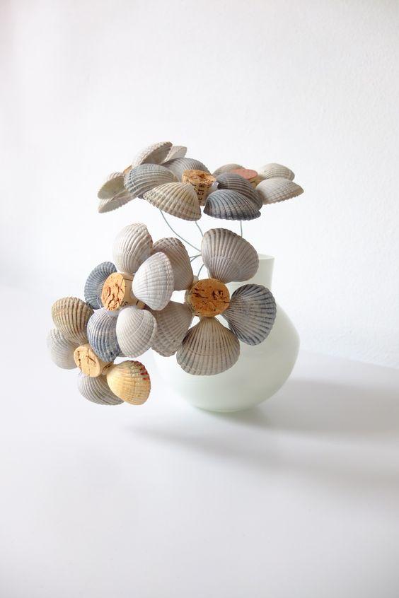 Bloem van schelpen. Lijm aan een halve kurk ong. 5 schelpen en maak een steel van metaaldraad.
