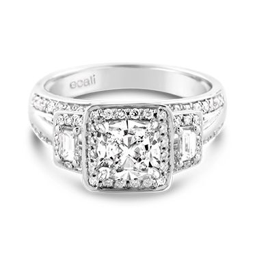 Ecali Presents: Showcasing uncompromising elegance is this round brilliant cut diamond accompanied by a pair of tapered baguette diamonds, each within their own diamond halo along a triple band.