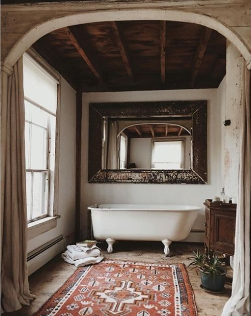 Vintage Persian rug with old plaster walls and a freestanding bathtub