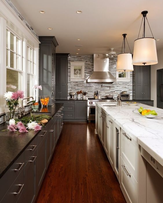 Plenty of gray cupboards paired with deep color countertops counters beautifully to the white counters with calacatta gold on top. It creates a style you won't want to miss.