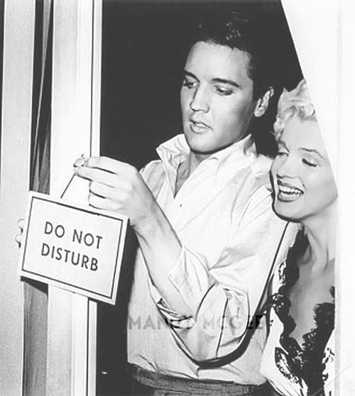 Here's a very rare publicity photo from 1957 of Elvis and Marilyn together outside of a motel room hanging a Do Not Disturb sign just for fun.
