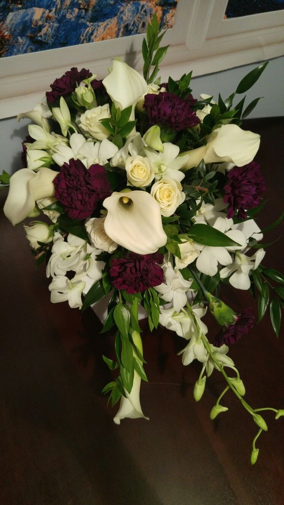 Elegant cascade bridal bouquet in ivory and dark purple. Callas, orchids, orchids and plum carnations. #Lighthouseflowershopmesa #Elegantplumandivoryflowers