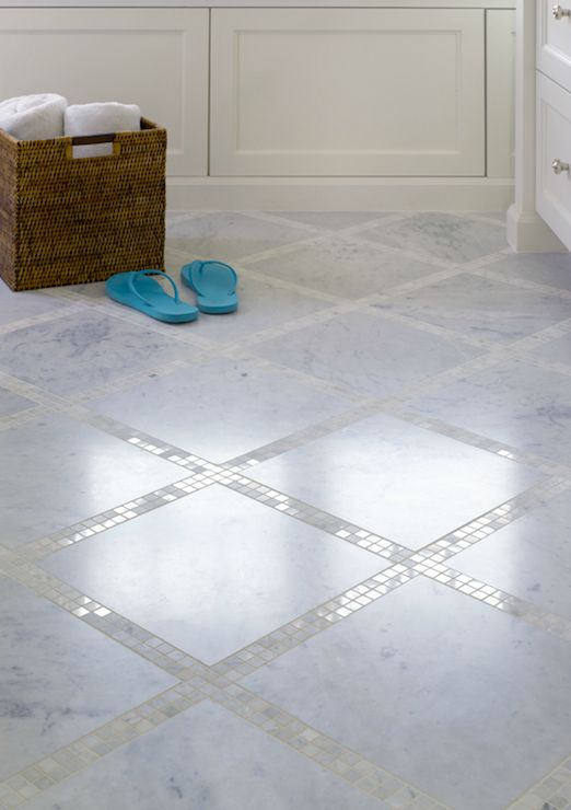 Bathroom floor with marble tiles and marble mosaic inset tiles.