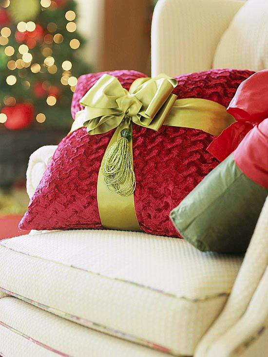 Buy pillows in holiday colors and then wrap them with ribbon to look like pretty Christmas packages.