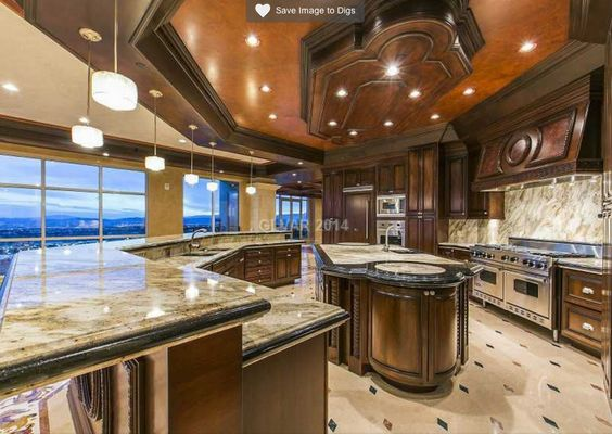 Deep wood in the cabinets and the two large islands as well as the ceiling give this room a designer look. Add the marble of the countertops and you've got yourself a winner in the luxury department.