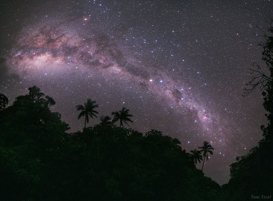 Milky Way Galaxy shines in this dark night sky above planet Earth's lush island paradise of Mangaia