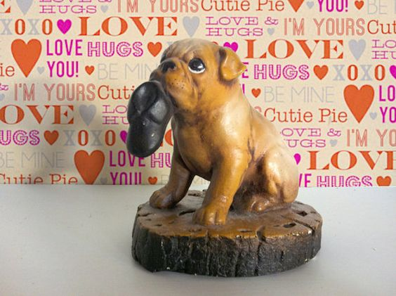 Vintage Chalkware Pug holding a slipper in his mouth.