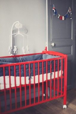 red crib, grey wall