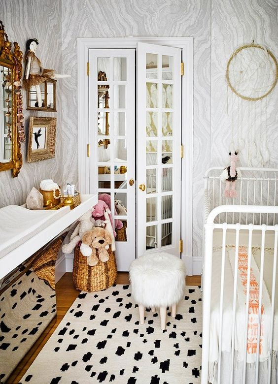 Feminine nursery with a metal crib, a faux fur stool, and marble wallpaper: