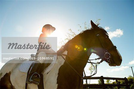 Boy riding horse in sunlight  – Imagem © CulturaRM / Masterfile.com: Fotografias, vetores e ilustrações criativas de arquivo para sites, telefones celulares e impressão.