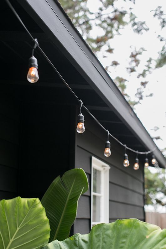 hanging globe lights against black home exterior on my patio / sfgirlbybay