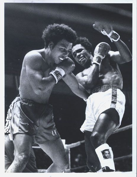 "February 5, 1977 at the Civic Center in Baltimore, Maryland local Olympic champion and future world champion Sugar Ray Leonard fought his professional debut against Luis ""Bull"" Vega. Leonard dominated the fight winning every round on the judges scorecards en route to taking a six round decision. Offered here is an original wire photo depicting action during the match and a close-up view of Leonard's shoe with his son's picture on it."