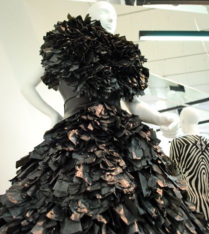 A photo of a female performer wearing an elaborate black dress made out of bin bags