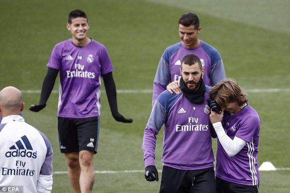 Modric shares a joke with Karim Benzema following the Frenchman's return to training