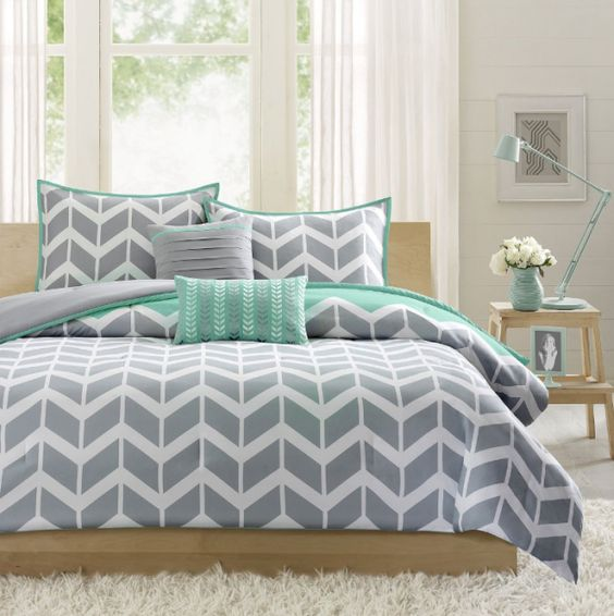 A chevron-print comforter set with teal accents.