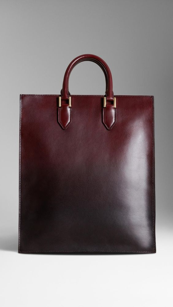 $1,795.00 Item 38933581 OXBLOOD         A portrait tote bag in hand-sprayed leather dégradé.         Inspired by traditional briefcase design, the bag has an internal partition and pockets.         Hand-stitched rolled leather handles feature polished metal hardware and graphic hand-painted edges.         36 x 42cm         14.2 x 16.5in         100% calf leather         Made in Italy