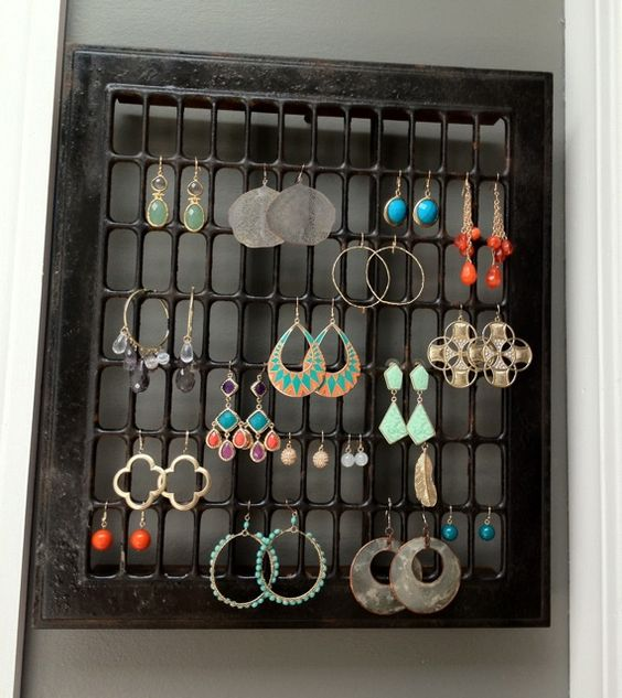 an iron grate transformed into an earring rack and hung on the wall!