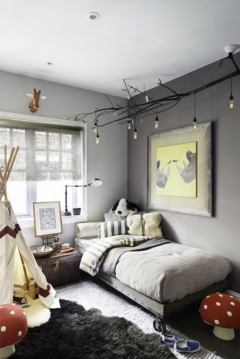 Whimsical boy's room features walls painted in two tones of gray along with a faux branch chandelier hanging over rhino art over Restoration Hardware Baby & Child Industrial Cart Platform Bed dressed in white and gray striped bedding beside vintage trunk doubling as nightstand and play teepee atop gray sheepskin rug layered over Land of Nod Rags to Riches Rug.