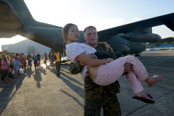 US Marine carries a woman injured by Typhoon Haiyan. (He seems more moved than she is)