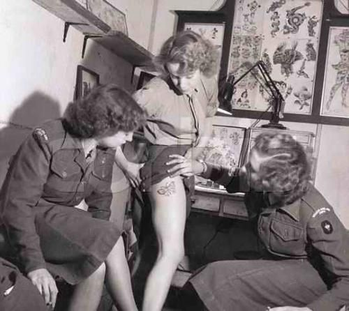 Woman in the British Royal Army Corps shows off her tattoo, 1940s.