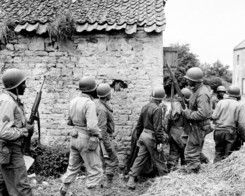 A platoon of black American soldiers surround a farm house in an unknown French town, searching for a German sniper who had been holding up the advance of the Allied invasion of Normandy, June 14, 1944.
