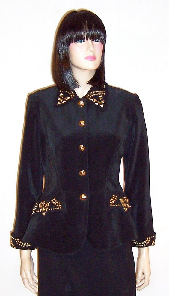 This is a fabulously designed black single-breasted jacket or blazer embellished with brass studs of varying sizes and shapes around each cuff, at each pocket, and around the collar, designed by Tadashi Shoji. It is fully lined, masterfully constructed, form fitting and flattering. The jacket is made of lycra and acetate, is in excellent vintage condition, and is marked a Size 8.