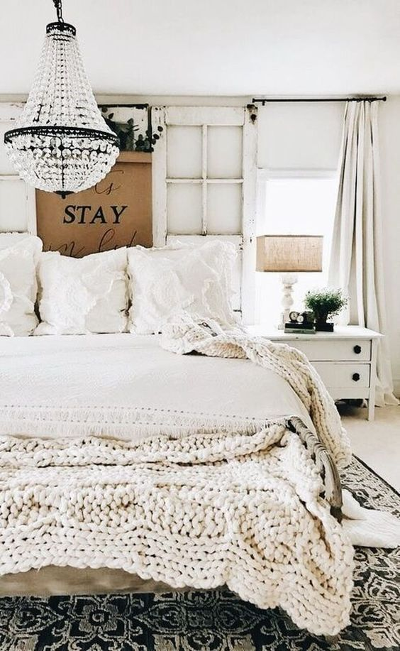 Bedroom interior design with black and white bohemian decor by Liz Marie blog. Empire style crystal chandelier, chunky knit throw, and white bedding. #bedroomdecor #whitebedroom #bohemian #rusticdecor #empirechandelier #shabbychic