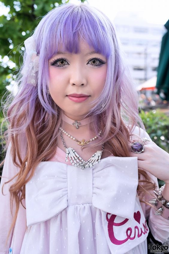 Moko is wearing a super kawaii big bow dress from the Harajuku brand Cerise with over-the-knee bow socks and Tokyo Bopper platform shoes – also with bows. Accessories include a pink choker, a Vivienne Westwood necklace, a skeleton hands necklace, several large rings, and several studded bracelets. Her pretty lavender hair with orange underdye also adds a lot to the cuteness of the look.