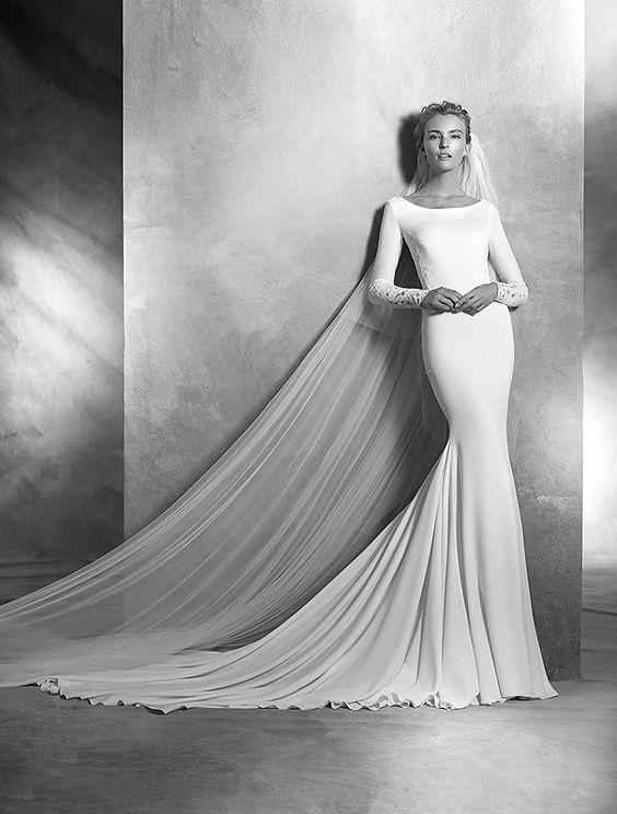 vania, collectie 2016 Van een stralende eenvoud, maar een hoge factor elegantie is in deze trouwjurk verwerkt. De boothals sluit prachtig aan bij de lange mouwen die gedeeltelijk met kant zijn. Om stil van te worden en een tikje gewaagd, als men de transparante kant ziet waar de blote rug mee is bedekt. De lange sleep is in volkomen harmonie met de jurk. En een lange sluier past perfect bij deze creatie. #exclusief #couture #zijde #atelierpronovias #koonings