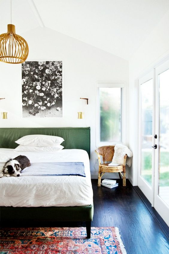 Modern bedroom with green upholstered bed and brass sconces.: