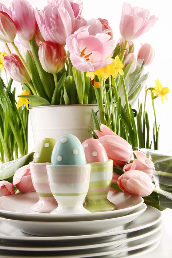 Easter eggs in cups with spring flowers on white...:
