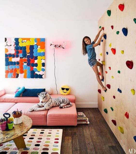 Ten-year-old Willow Romanek climbs a rock wall in the playroom.