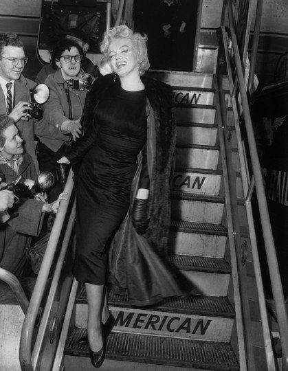 Marilyn Monroe mugs for the paparazzi at New York's Idlewild Airport (now JFK) as she boards an American Airlines flight headed for Hollywood in 1956.