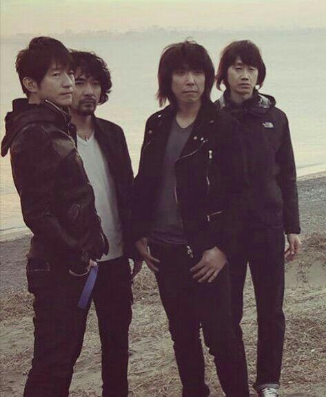 浜辺に立つ四人のmr.childrenの壁紙