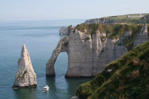 """Take a hike through Étretat, France and stop to gaze at its world-renowned cliffs, including 3 natural arches and the pointed """"needle"""". These cliffs and the associated resort beach attracted artists including Eugène Boudin, Gustave Courbet and Claude Monet, and were featured prominently in the 1909 Arsène Lupin novel The Hollow Needle by Maurice Leblanc. #JetsetterCurator"""