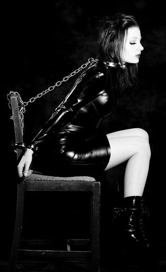 Latex catsuit. Collar. Handcuffs. Chains.