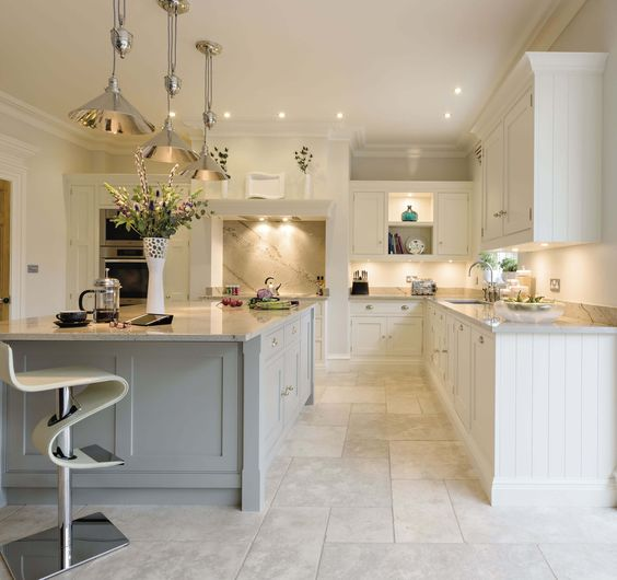 White Kitchens We Can't Stop Pinning! This open plan kitchen is the perfect space for family dining, with feature island and bespoke storage solutions complemented by Miele appliances. #whitekitchen #classic #greyisland