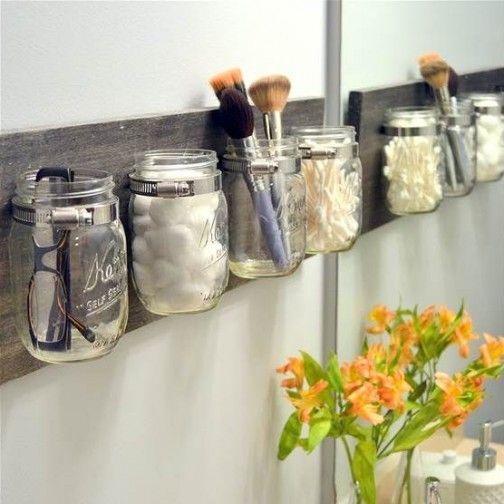 Pots en verre accrochés au mur pour mettre des rangements dans la salle de bain
