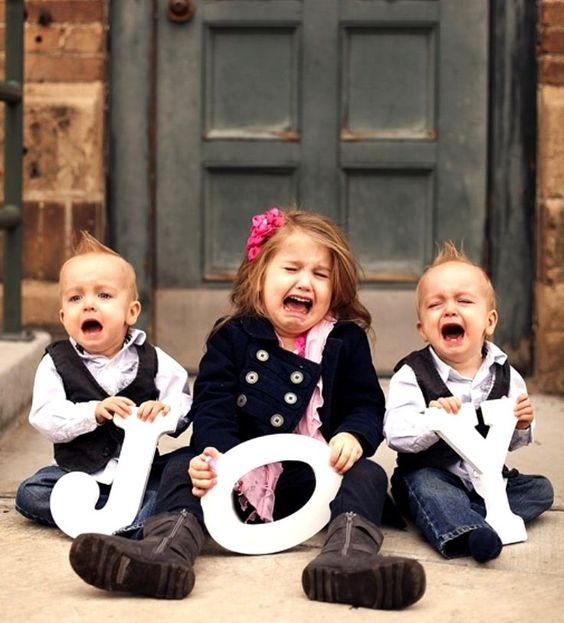 funny family holiday photo ideas - crying children holding JOY sign.