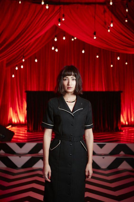 黒いワンピースを着た赤いステージの前に立つ佐田真由美の画像