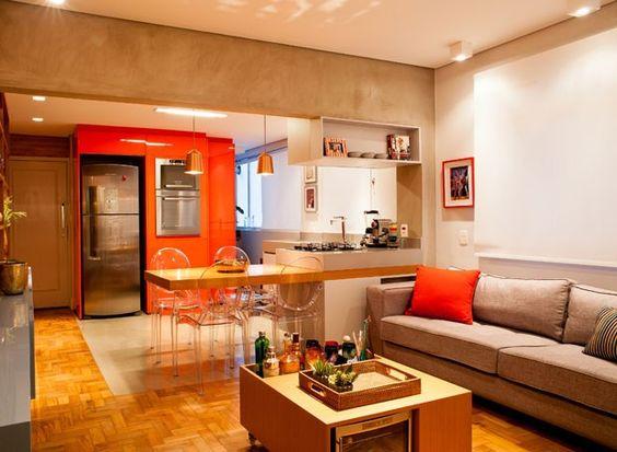 Sala e cozinha foram integradas criando uma área social mais ampla. O piso de taco de madeira é original do imóvel e foi restaurado na reforma. (Foto: André Santana/Divulgação)