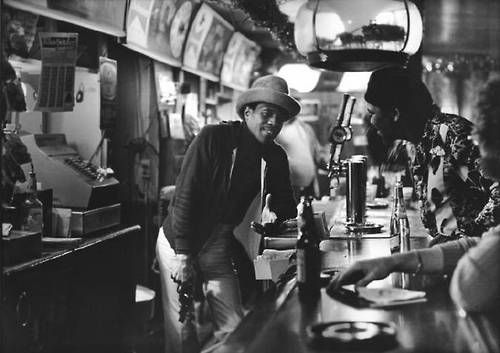 Blues legend Junior Wells tends bar (with pistol) at Theresa's Lounge, 4801 S Indiana Ave, 1979, Chicago. Marc PoKempner