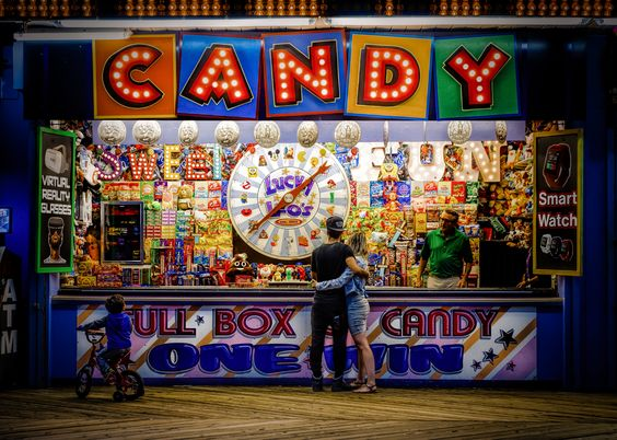 """https://flic.kr/p/Hx3hMT   Lucky Leo   A couple in love tries their hand at a spin wheel game on the boardwalk in Seaside Heights, New Jersey while a mesmerized child looks on. Classic scene if you're familiar with the """"jersey shore."""" Summer of 2016."""