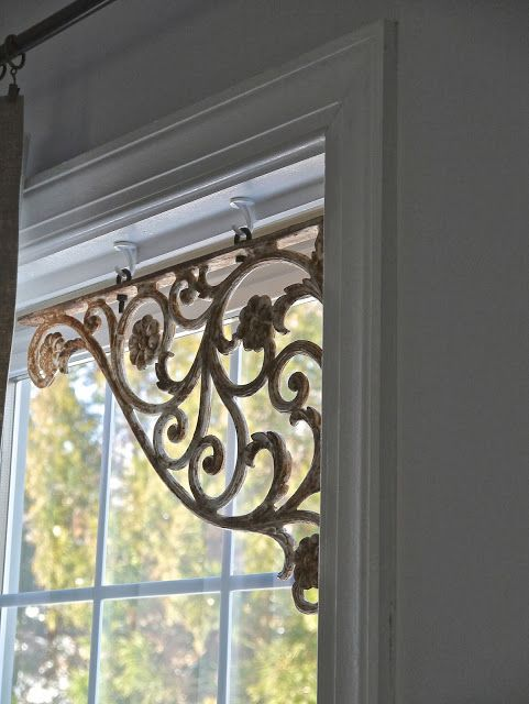 Repurposed Vintage Iron Brackets - simply hung on window frame's interior by cup hooks. This is a clever way to add interest to a room.