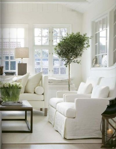 white living room; white slipcovers, sea grass rug and indoor plant. heaven.:
