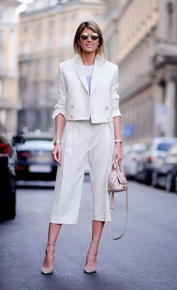 Helena Bordon parada no meio da rua e dos carros posa para foto vestindo conjunto de alfaiataria off white de risca de giz, com calça pantacourt, scarpin nude, bolsa nude e óculos redondo dourado: