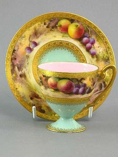ROYAL WORCESTER FRUIT PAINTED PEDESTAL CUP AND SAUCER, c1921, each decorated with a band of fruit between embossed gold borders, on green and pink ground, 11cms diameter. Est. R500 - 750