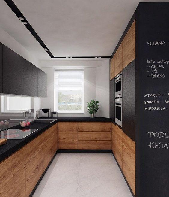 cuisine en U petite surface avec armoires en bois sans poignées et surfaces noires mates