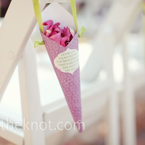 Colorful paper cones filled with flower petals for guests to throw during the recessional hung from the ceremony chairs.